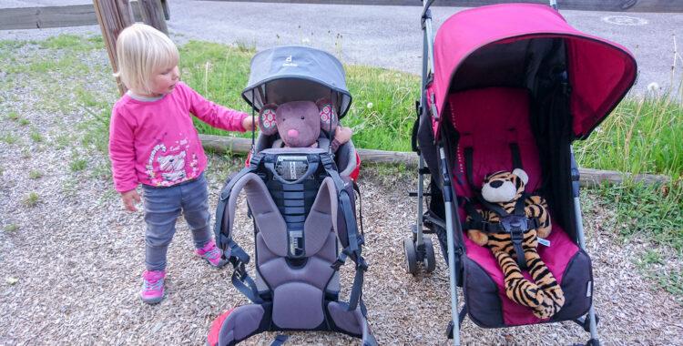 Kleinkind mit Kraxe und Buggy